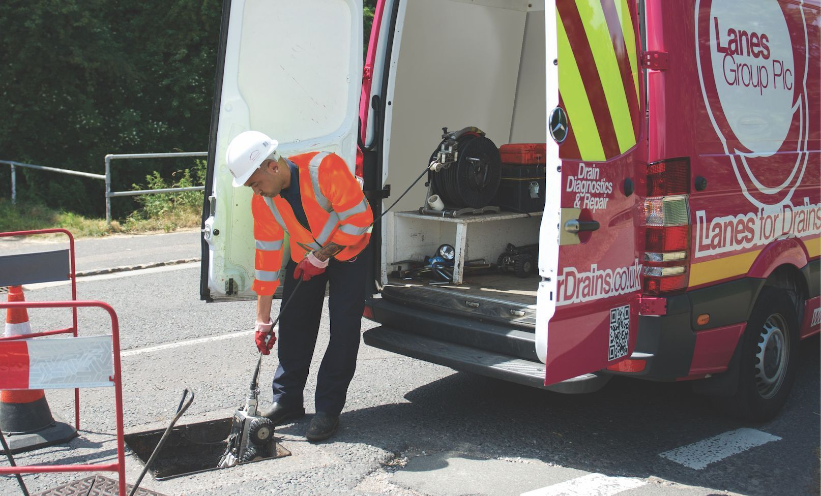 Lanes Group engineer standing beside a Lanes Group van carrying out a CCTV survey of a sewer beneath the road