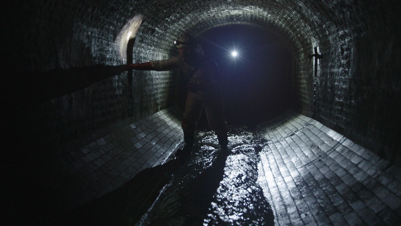 The inside of a dark sewer, with an engineer inspecting the sewer wall with a torch