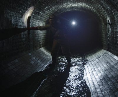 A drainage engineer walking inside of a sewer