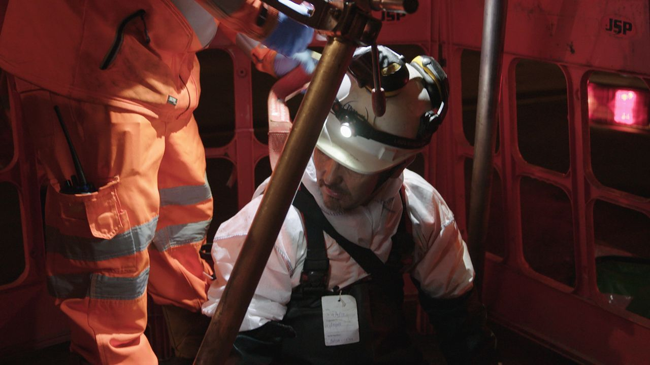 Lanes Group engineer in a hard hat with torch entering a sewer