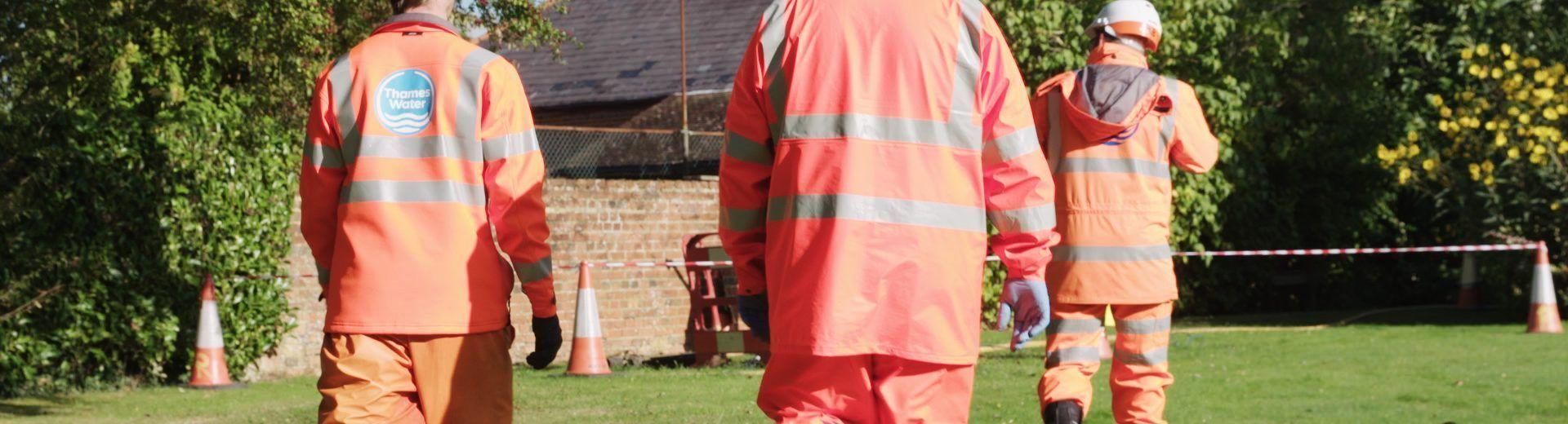 Three engineers in orange high vis walking to site