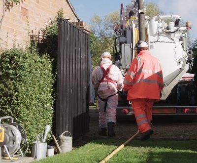 Two engineers walking towards tanker unit on residential property
