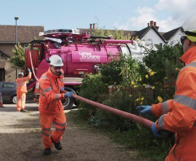 Drainage engineers dressed in high-visibility workwear using a jet vacuumation tanker unit