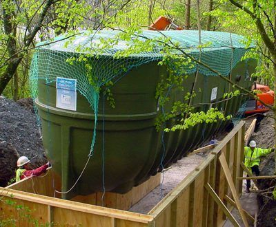 A septic tank being installed in a clearing