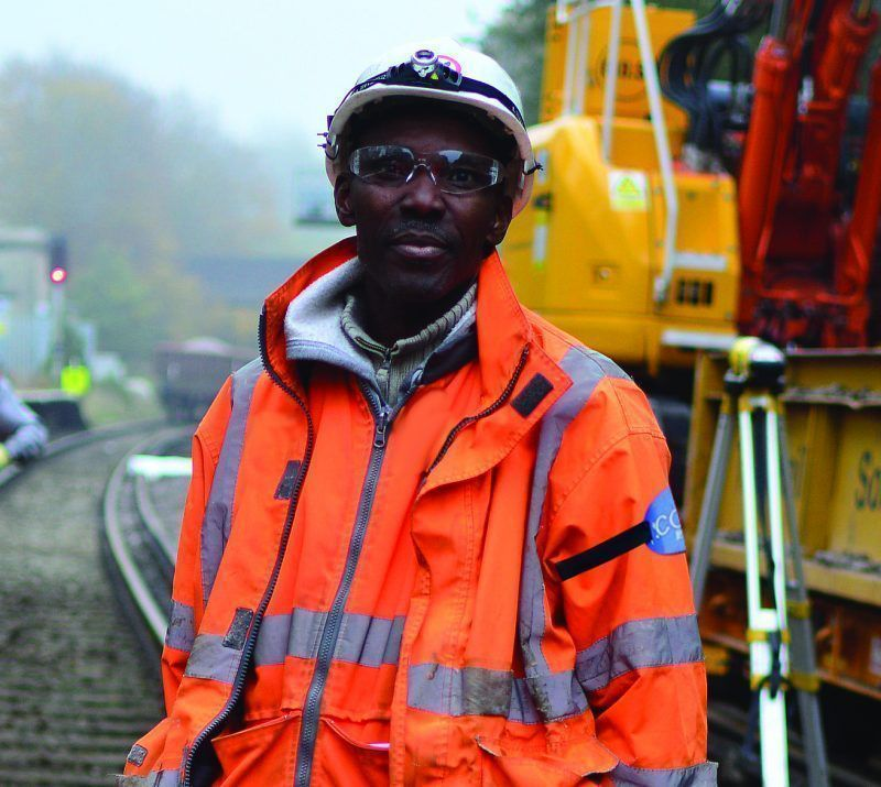 Engineer on railway wearing orange high visibility jacket, hard hat and eye protection