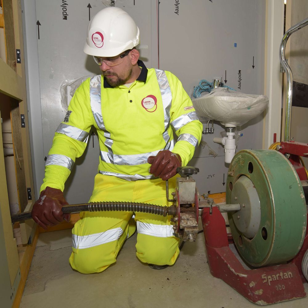 Lanes worker in high visibility clothing carries out electro-mechanical cleaning in Aberdeen Hospital