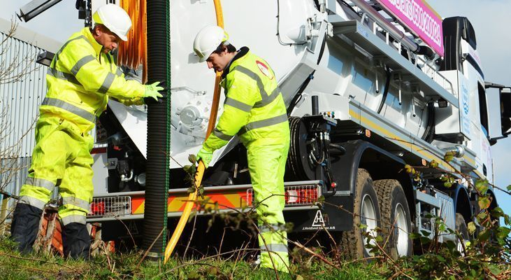 Two Lanes Group engineers in high vis protective clothing operating a jet vacuumation tanker off road