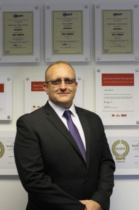 Chris Wilde of Lanes Group standing in front of accreditations