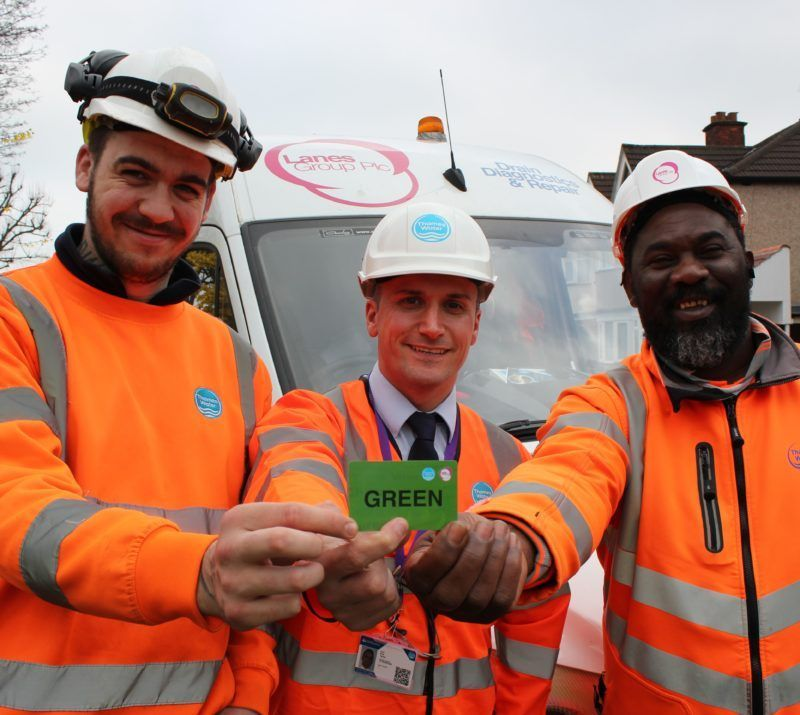 Drainage engineers holding green health and safety card