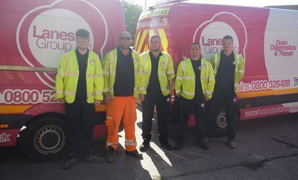 Group of engineers in high vis gear standing in front of Lanes Group PLC branded vans