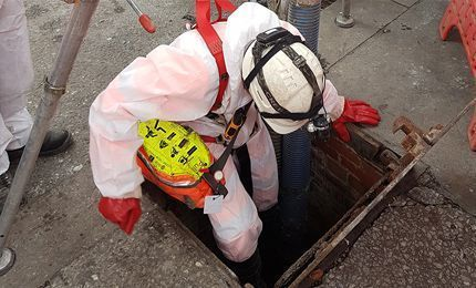 Engineer in white overalls and hardhat entering a drain