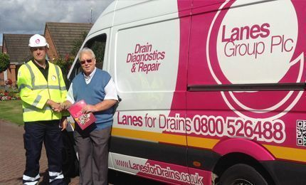 Engineer in yellow high vis jacket shaking hands with customer next to a Lanes Group PLC branding van