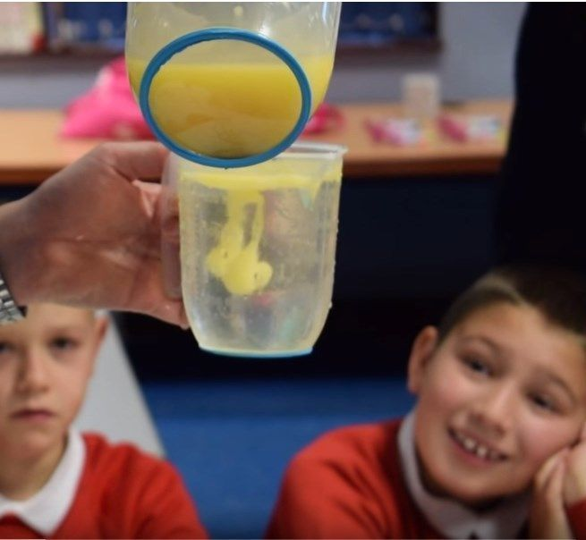 Students watching fat being poured into a liquid as part of a science experiment at school