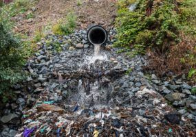 Polluted drain flowing into a river