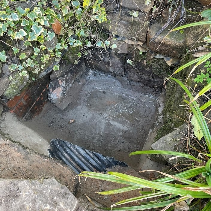 The sump in the neighbour's garden that catches water as it comes in through the stone wall